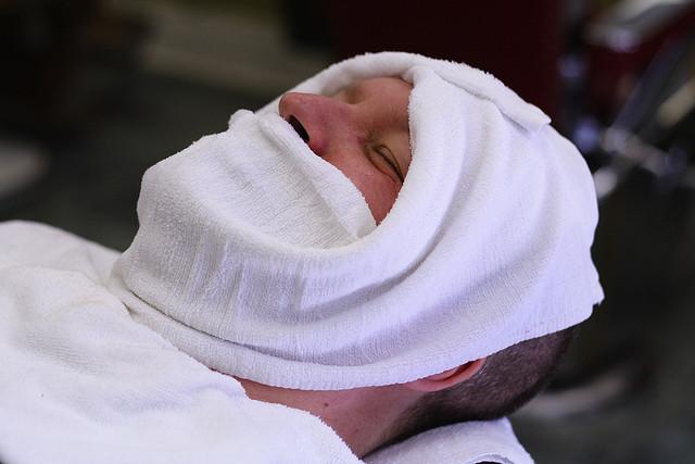ホットタオルで髭を蒸す男性