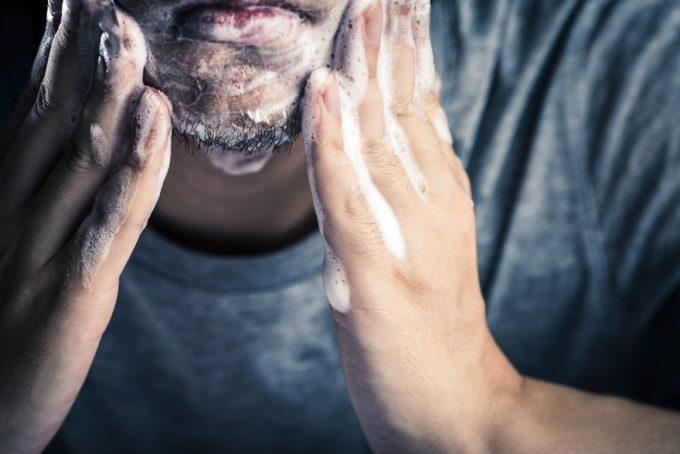 髭剃り前に洗顔する男性