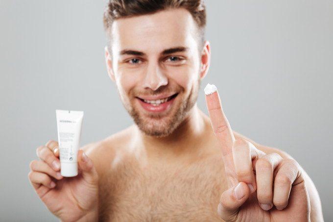 洗顔後にクリームを塗る男性